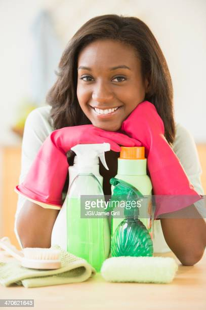 Black woman smiling with cleaning products