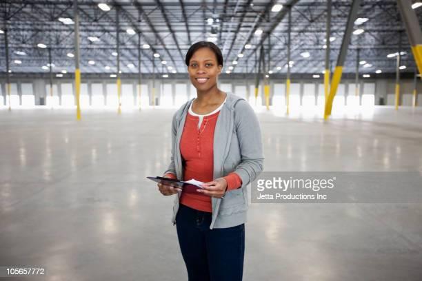 Black woman standing in empty warehouse