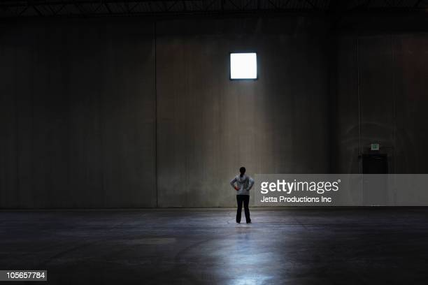 Black woman standing in empty warehouse