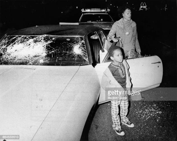 A black woman stands with her young son next to her car which had been stoned by a group of white youths on the American Legion Highway in Boston's...
