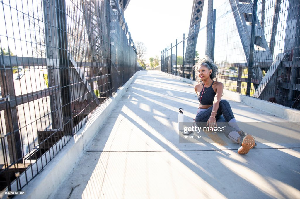 A Black Woman Stretching in the City : Stock Photo