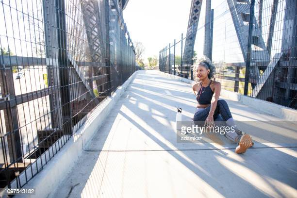 a black woman stretching in the city - lower back stock pictures, royalty-free photos & images
