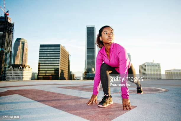 black woman stretching legs on urban rooftop - helipad stock photos and pictures