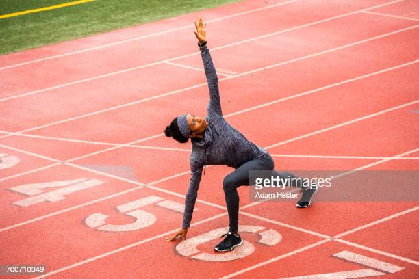 black woman stretching on track starting line - オリンピック選手 ストックフォトと画像