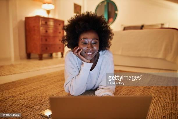 zwarte vrouw die het net op haar laptop thuis surft] - afro amerikaanse etniciteit stockfoto's en -beelden