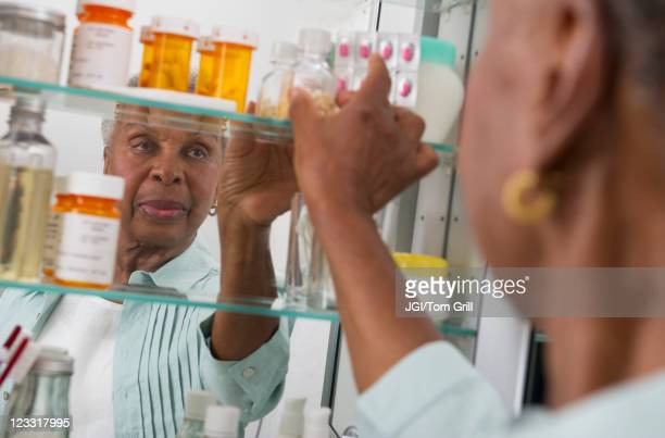 black woman taking medication from cabinet - medicine cabinet stock pictures, royalty-free photos & images