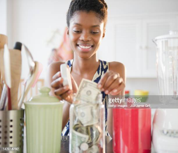 Black woman taking money out of jar
