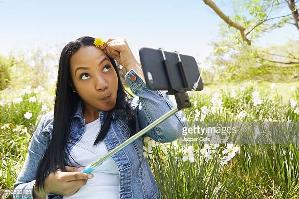 Black woman taking self portrait in park