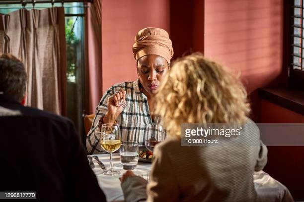 black woman tasting food in restaurant - headdress stock pictures, royalty-free photos & images