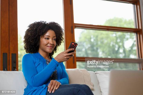 Black woman texting on cell phone on sofa