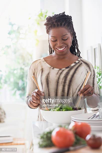 Black woman tossing salad in kitchen