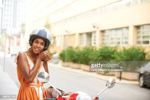 black woman tying on helmet - motor scooter stock pictures, royalty-free photos & images
