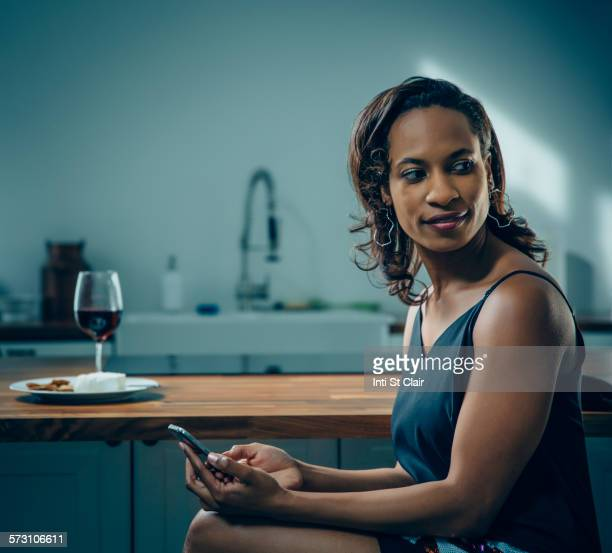 Black woman using cell phone at kitchen counter