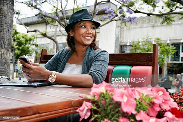 Black woman using cell phone at sidewalk cafe