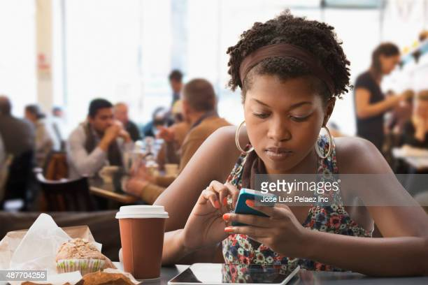 Black woman using cell phone in cafe