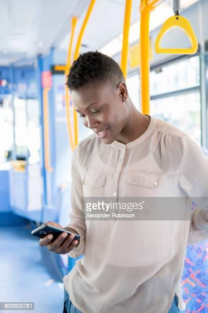 black woman using cell phone on bus - vertical red tube fotografías e imágenes de stock