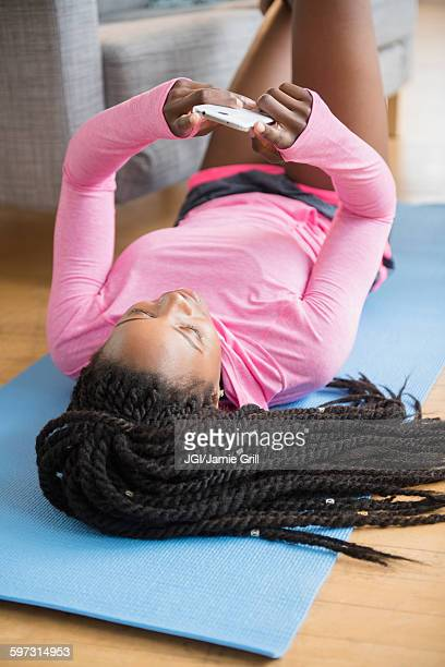 Black woman using cell phone on yoga mat
