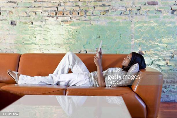 Black woman using digital table on sofa in living room