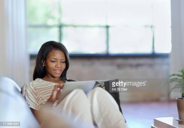 Black woman using digital table on sofa in living room