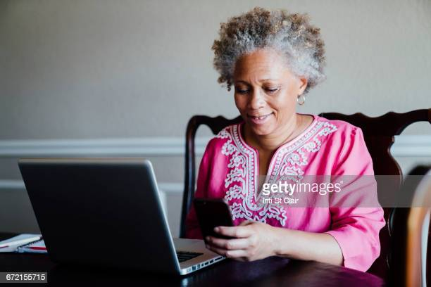 Black woman using laptop and cell phone at table