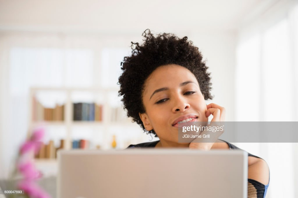 Black woman using laptop at table : Stock Photo