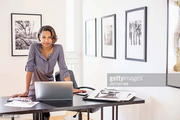 black woman using laptop in art gallery office - leaning stock pictures, royalty-free photos & images