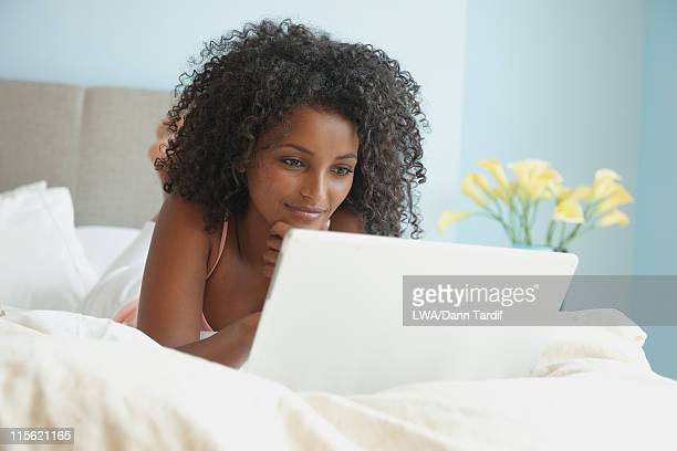 Black woman using laptop in bed