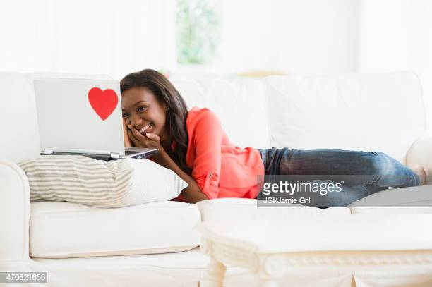 black woman using laptop on sofa - valentines african american stock pictures, royalty-free photos & images