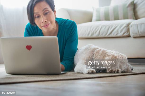 Black woman using laptop with dog