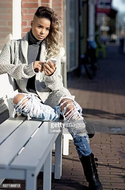 black woman using phone outdoors