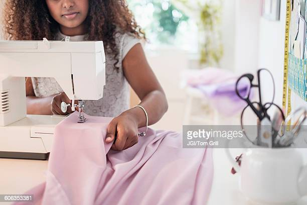 Black woman using sewing machine