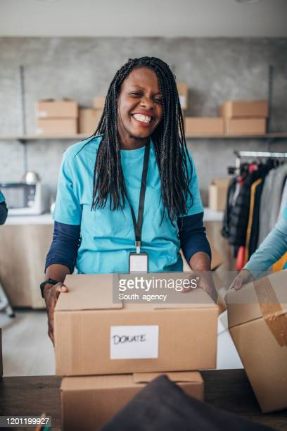 black woman volunteer packing donation boxes in charity food bank - homeless shelter stock pictures, royalty-free photos & images
