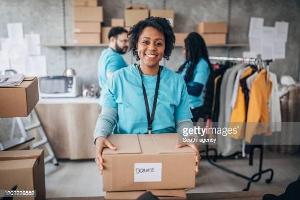 チャリティーフードバンクで寄付箱を梱包する黒人女性ボランティア - ホームレスシェルター ストックフォトと画像
