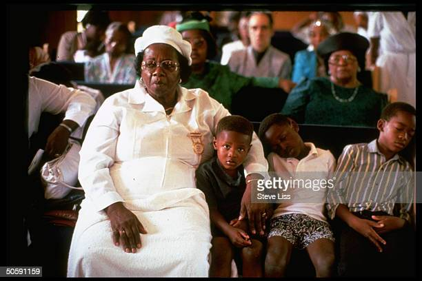 Black woman w inattentive boys attending service at Rose Hill Church