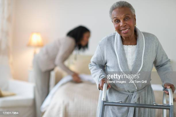 Black woman walking with walker in bedroom