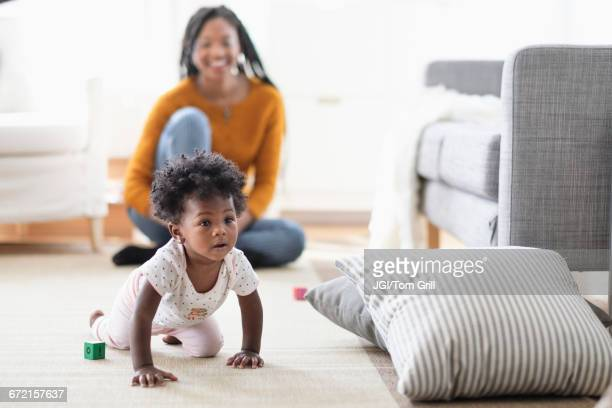 black woman watching baby daughter crawl toward pillow - life events stock pictures, royalty-free photos & images