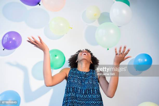 Black woman watching falling balloons