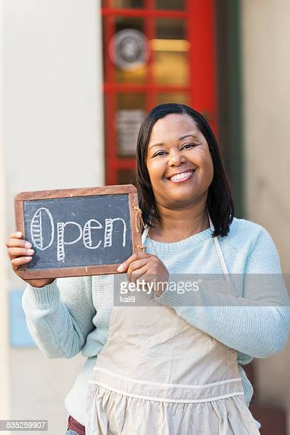 Black woman wearing apron holding OPEN sign