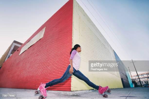 Black woman wearing roller skates gliding around corner