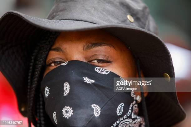 A black woman wears a mask while protesting against the KKK Hundreds of counter protesters including the Nation of Islam New Black Panthers and Huey...