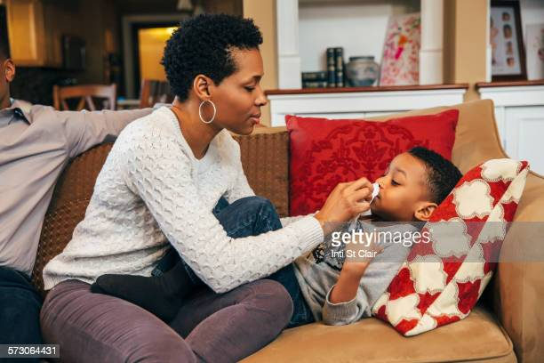Black woman wiping nose of son on sofa