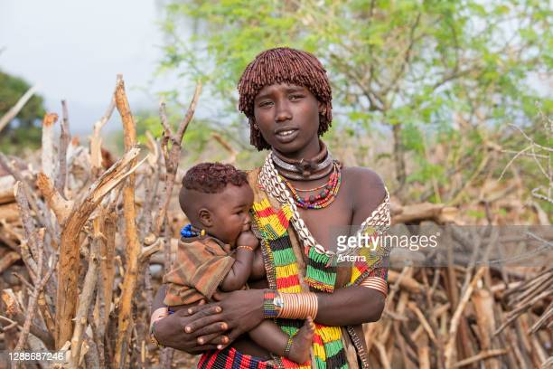 Black woman with child of the Hamar / Hamer tribe in village in the Omo River valley, Debub Omo Zone, Southern Ethiopia, Africa.