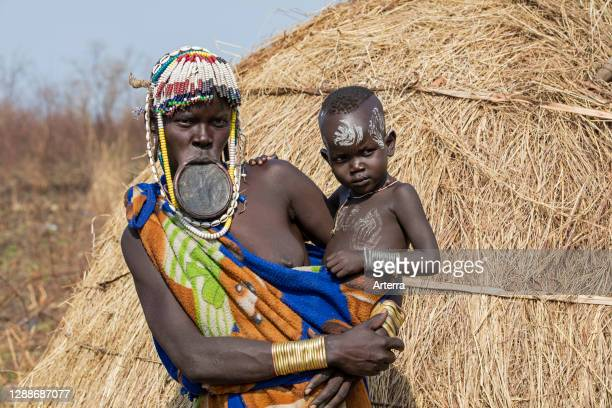 Black woman with child of the Mursi tribe wearing lip plate and beads in the Mago National Park near Jinka, Debub Omo Zone, Southern Ethiopia, Africa.