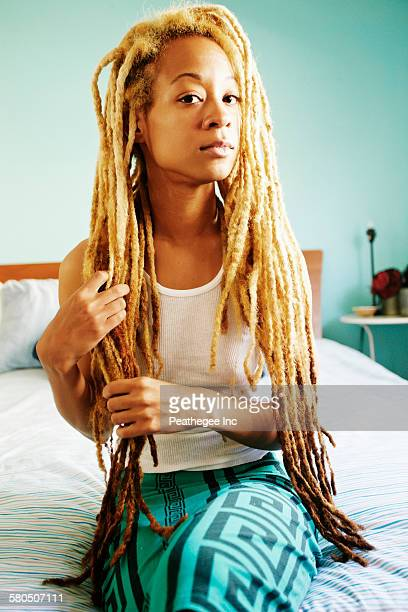 Black woman with dreadlocks sitting on bed