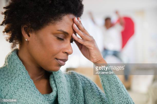 Black woman with headache and playful son in background