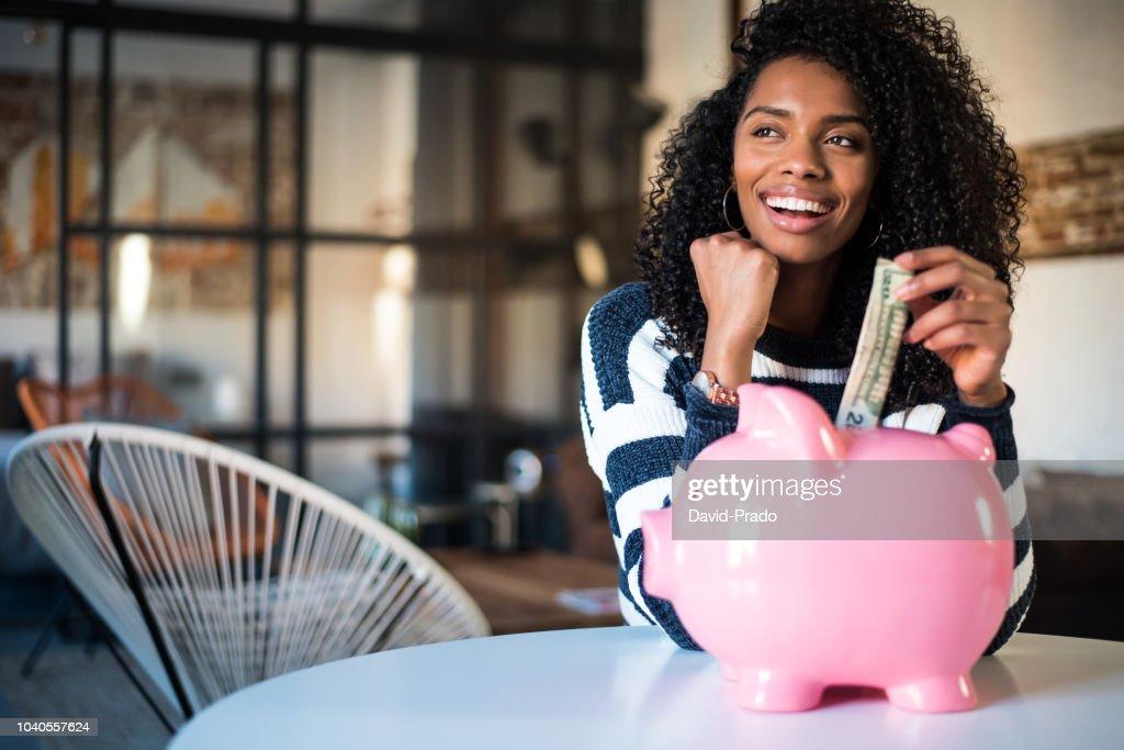 Black woman with saving piggy bank : Stock Photo