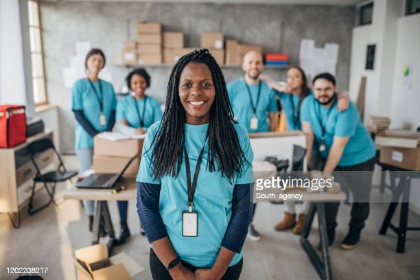 black woman with volunteers friends in charity food bank - charity and relief work stock pictures, royalty-free photos & images