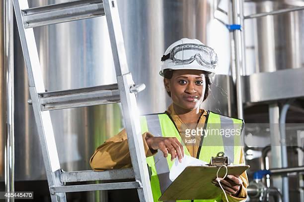 Schwarze Frau bei der Arbeit in Fabrik mit Zwischenablage, Bauarbeiterhelm
