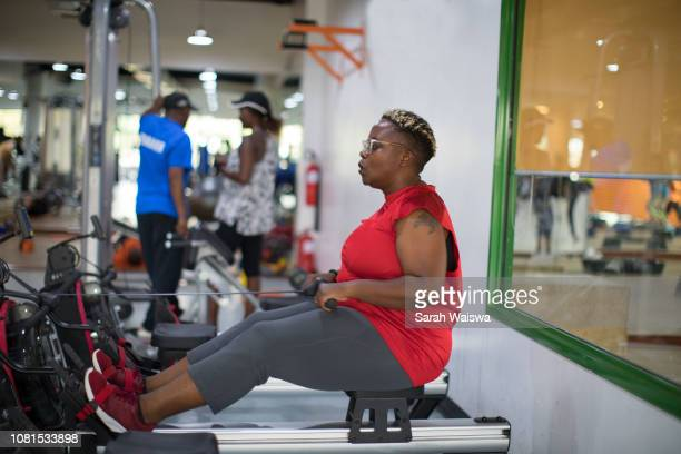 black woman working out on a rowing machine at the gym - sarah hardy stock pictures, royalty-free photos & images