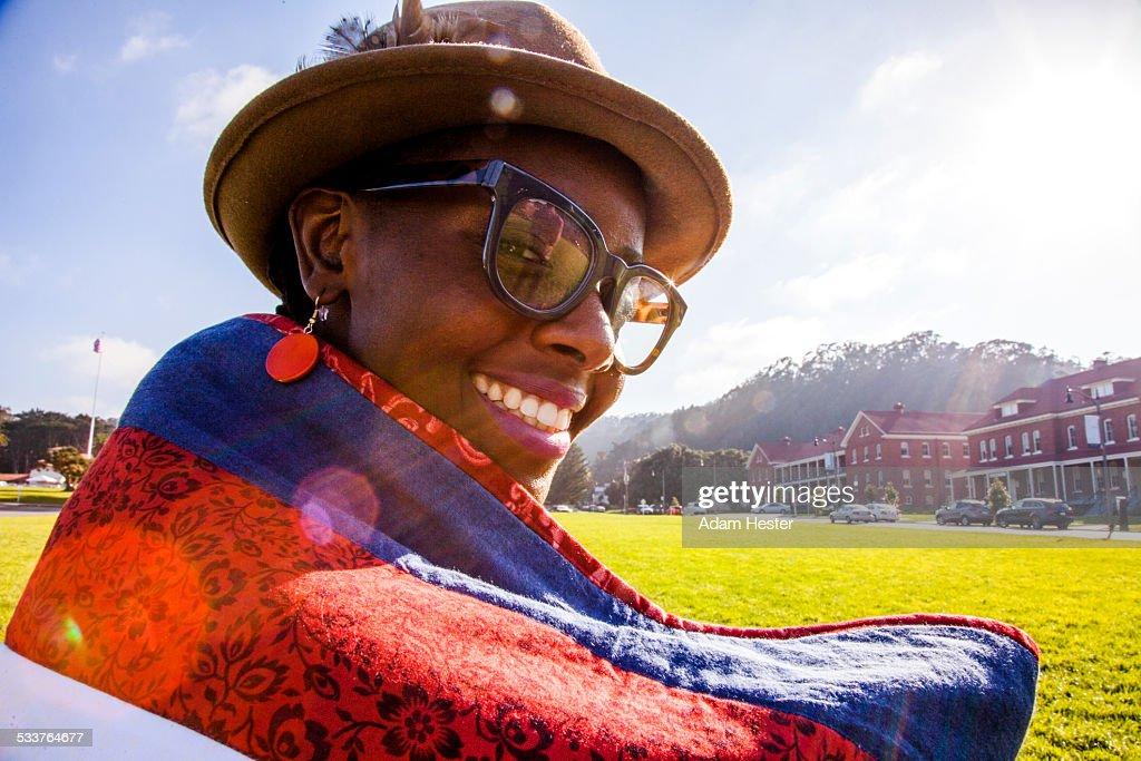 Black woman wrapped in blanket in urban park : Foto stock